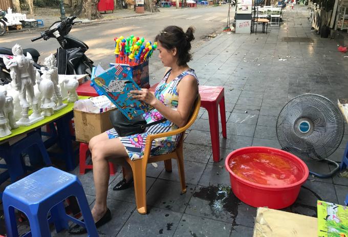 Một phụ nữ lao động tại hè phố chống nóng bằng cách sáng tạo chiếc quạt khá nước từ thau chứa đá lạnh và chiếc quạt điện đơn sơ.
